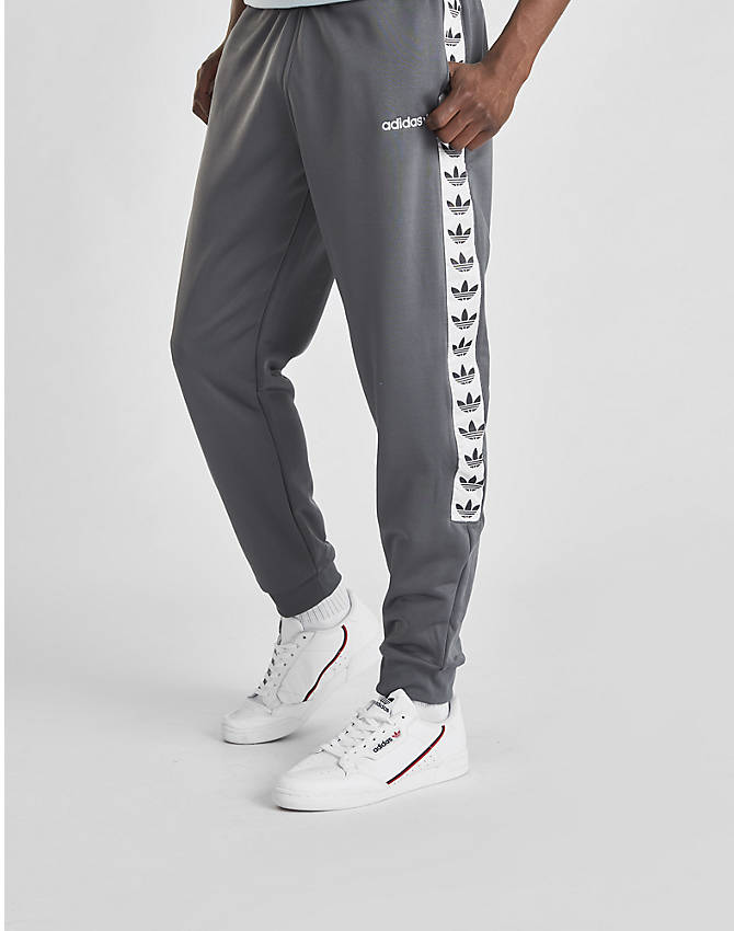 Front Three Quarter view of Men's adidas Originals Tape Poly Track Pants in Grey